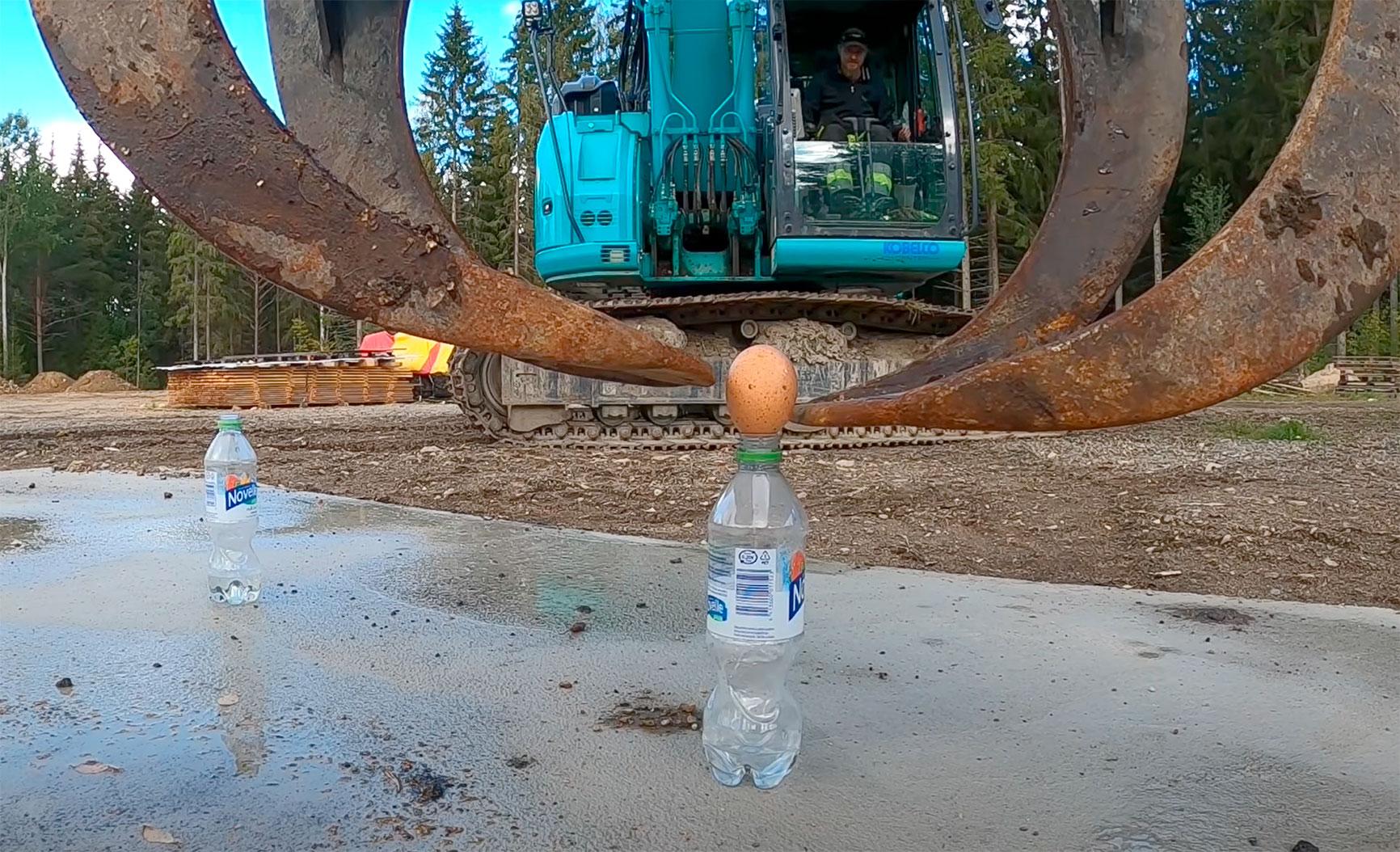 Esa-Pekka Penttilä tarttui haasteeseen, ja kokeili, onnistuuko raa'an kananmunan siirtäminen kaivinkoneella pullon suulta toiselle. Kuvakaappaus Penttilän kuvaamalta videolta.