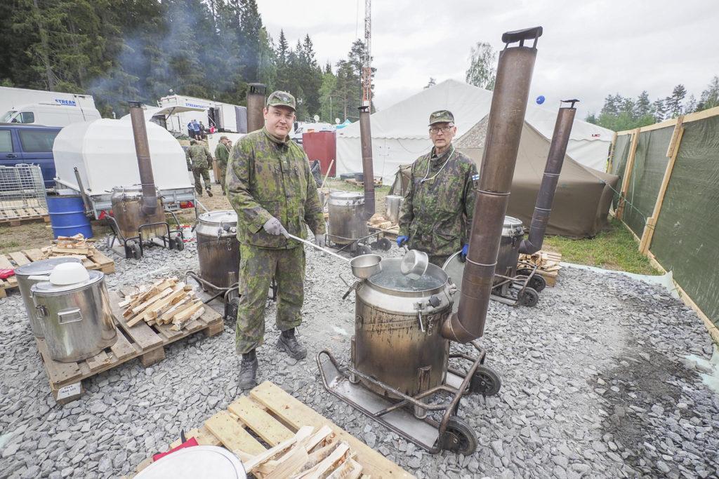 Maanpuolustusväki vastaa talkooravintolan kahvista ja aamupuuroista. Kenttäkeittimen äärellä ovat Jere Virtala ja Ari Loppi.