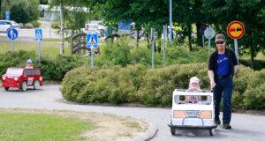 Kokon perheen tyttötrio innostui polkuautoilusta Rahtarit-liikennepuistossa. Oskari-isä antoi työntöapua Lotalle. Punaista autoa ajaa Jenna. Suojatiemerkin takaa pilkistää Taina.