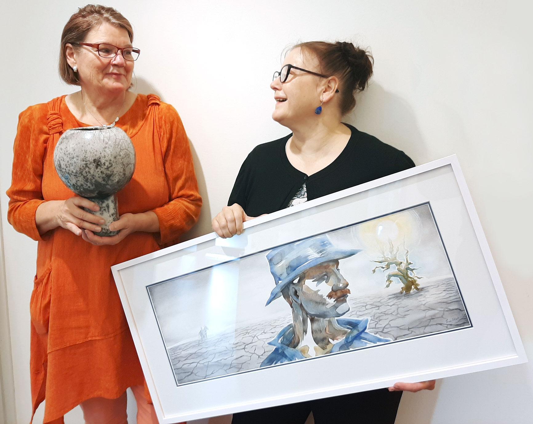 Liisa Turunen ja Ina Jaakkola sanovat olevansa sielunsiskoja. Turusella kädessään rakutekniikalla toteutettu Kehtolaulu-teos ja Ina Jaakkolalla Vääriä valintoja ja huonoja sattumia 1 -maalaus.