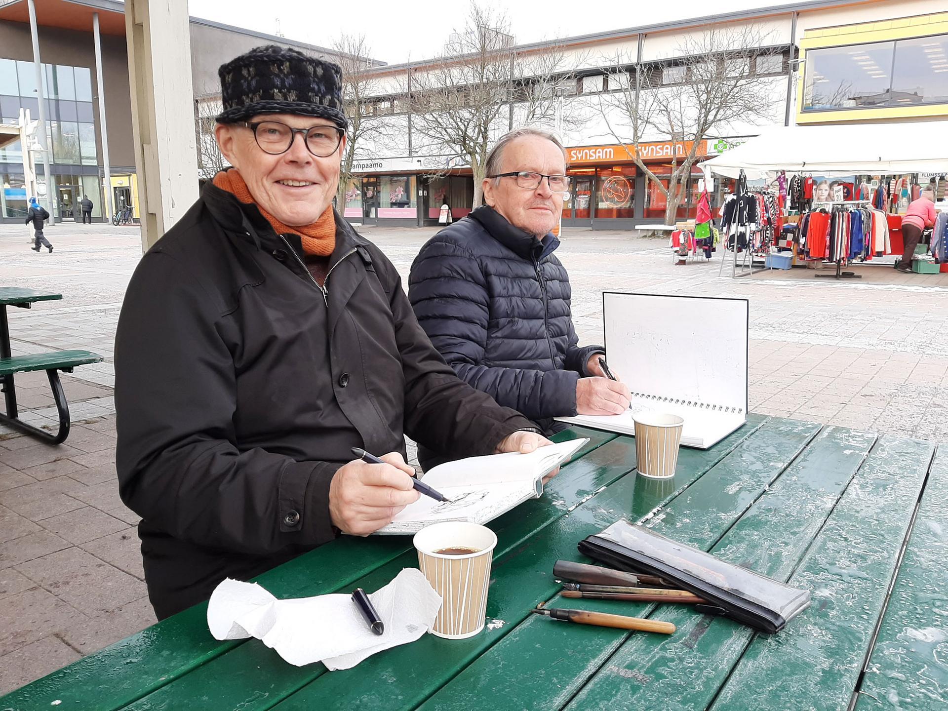 Markku Lahtinen ja Olli Mäkelä pitivät kahvitauon näyttelynsä ripustuksen välissä – missäs muualla kuin torikahviossa näkymiä piirrellen.
