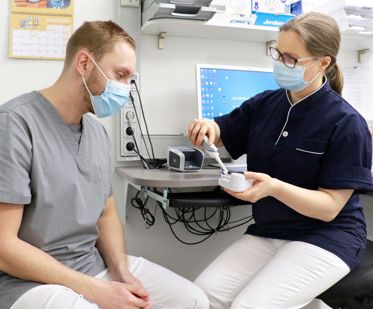 Lavastetussa kuvaustilanteessa hammaslääkäri Enni-Maria Junnila kertoo kollegalleen Pasi Karhatsulle, miten hampaat harjataan oikeaoppisesti.