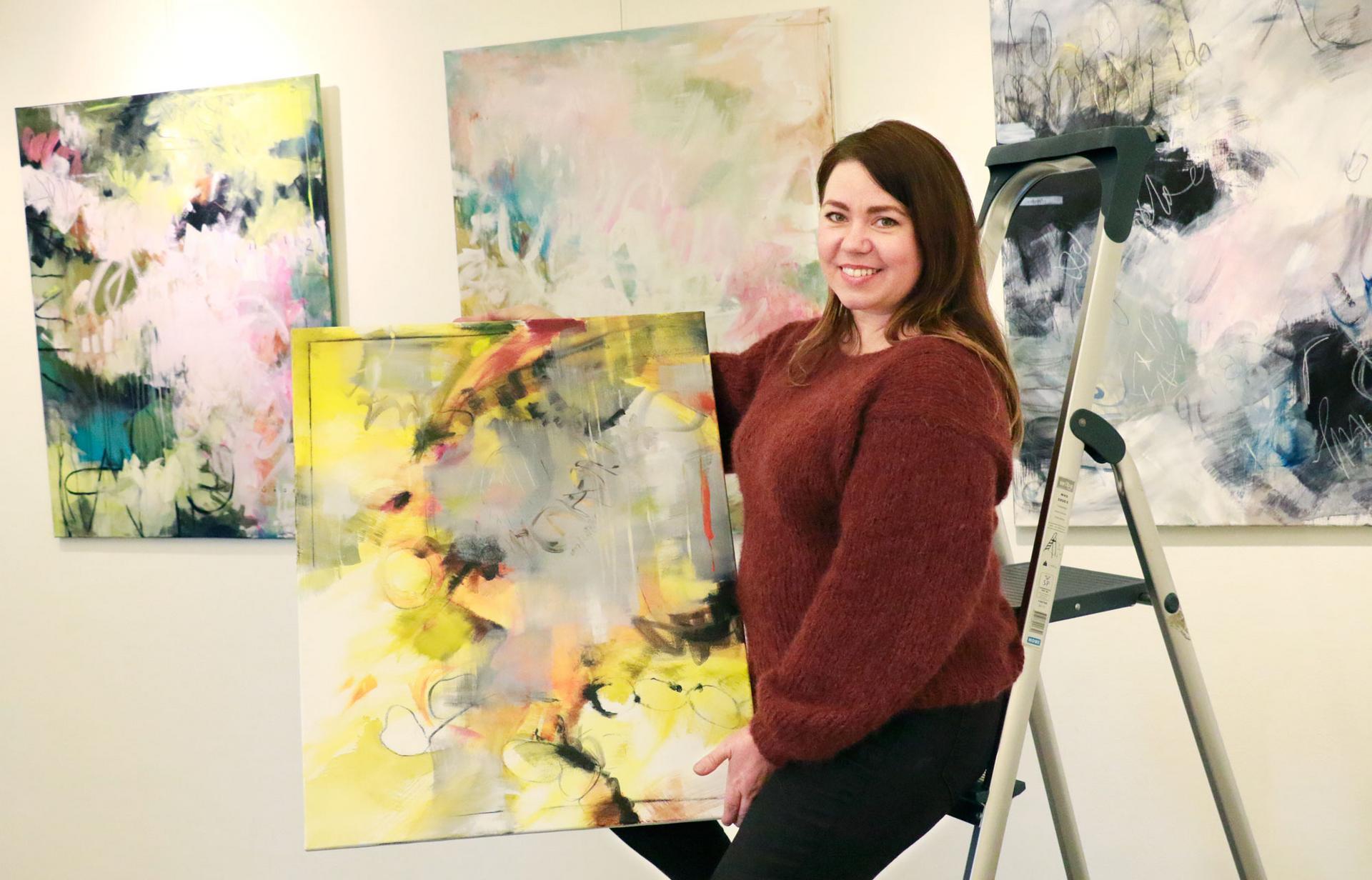 Säde Numminen maalaa akryyliväreillä abstrakteja töitä.