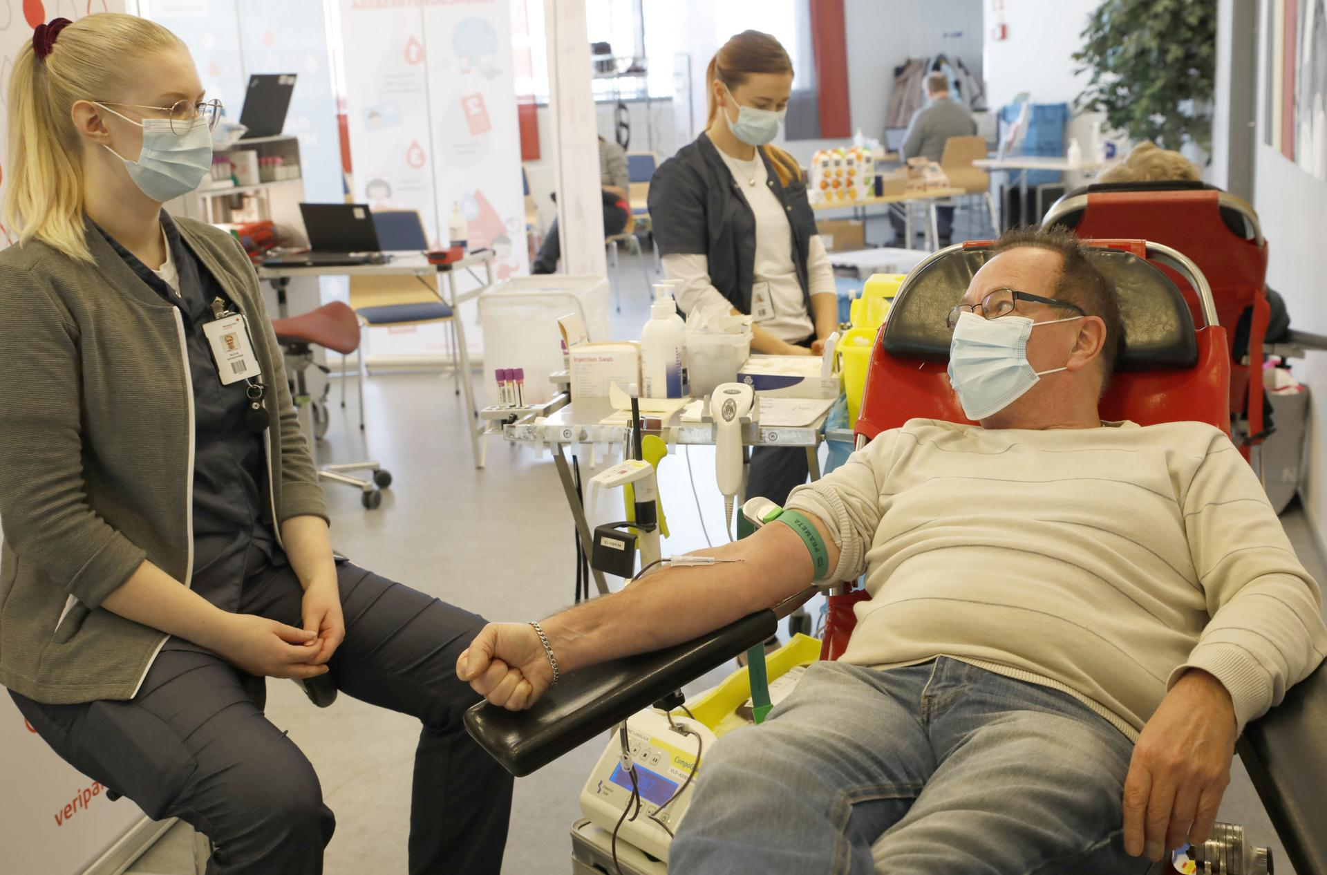 Jukka Kannusmäki ottaa verenluovutuksen rennosti. Sairaanhoitaja Noora Virtanen kertoo, että veripalvelun työntekijöillä on taito rentouttaa luovutusta jännittävät ihmiset.